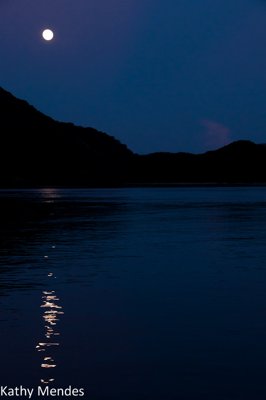 The full moon setting over the islands.