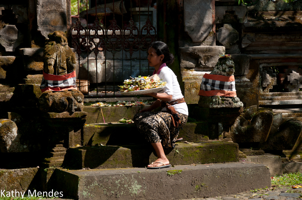 Woman putting out offerings in Ubud.