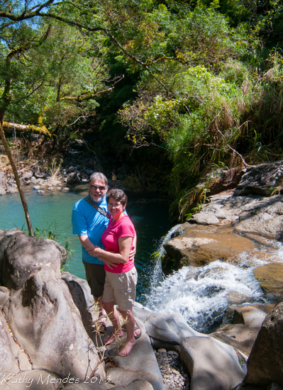 Randy and Kathy on the edge of a waterfall flowing into an emerald green jungle pool.
