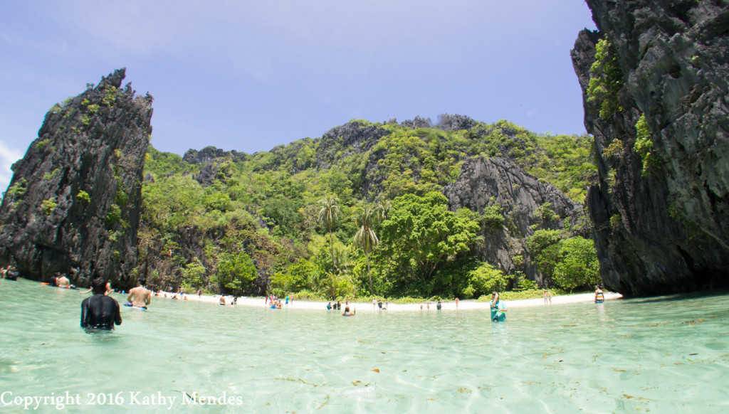 "Tourists at one of the ""secret"" coves on the beach surrounded by the beautiful black limestone cliffs and jungle."